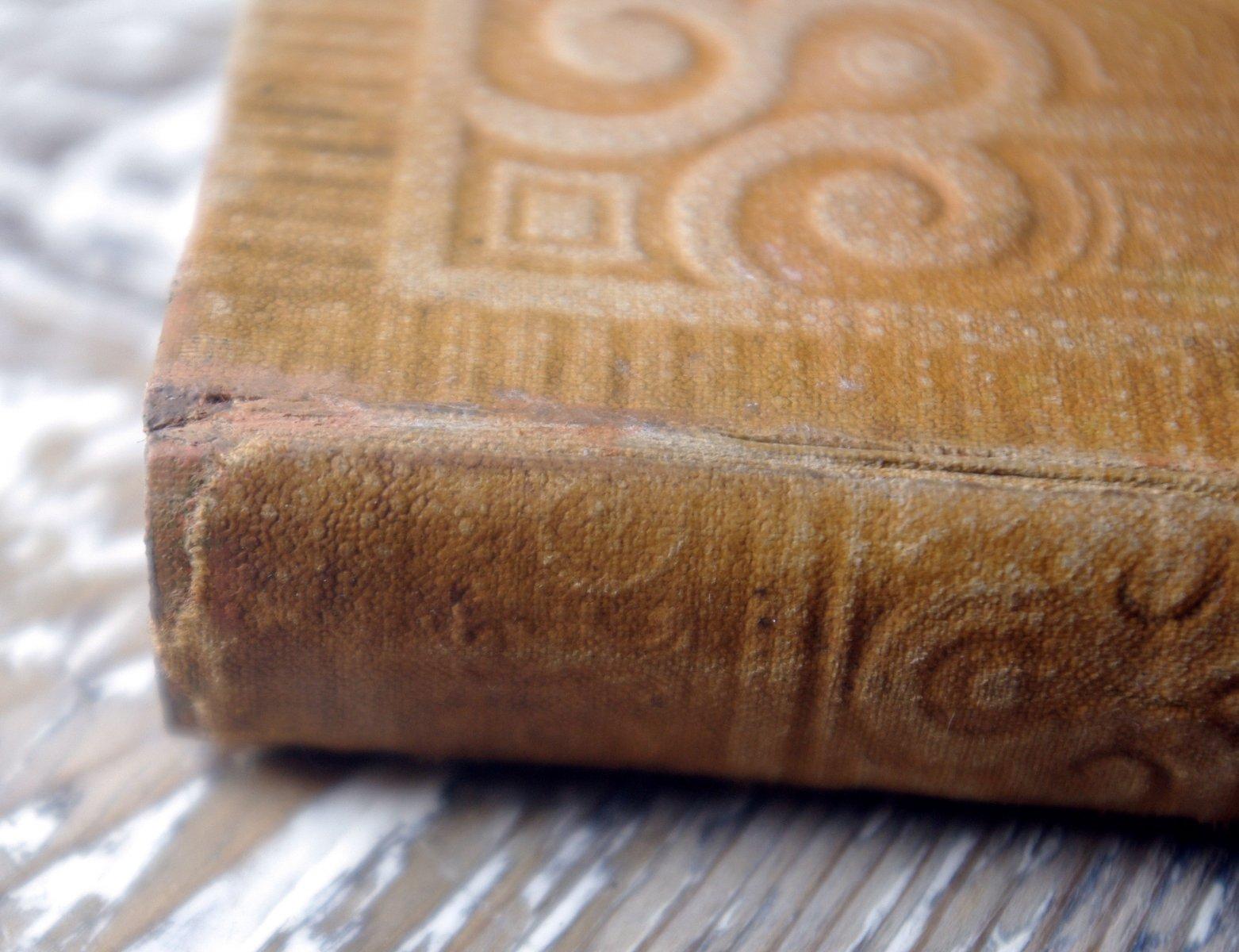 Фрагмент отреставрированного переплета Евангелия 1895 года издания. У издания был оторван корешок. На фото видна затонированная основа, на которую наклеен оригинальный корешок.