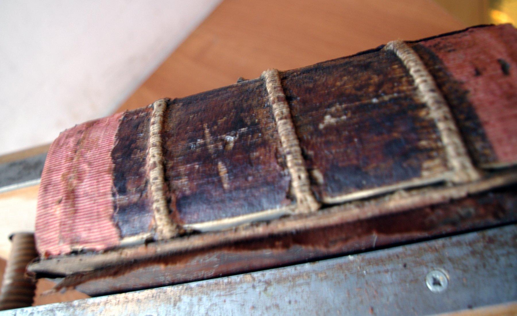 Псалтирь 19 века во время реставрации. Общий вид корешка со шнурами.